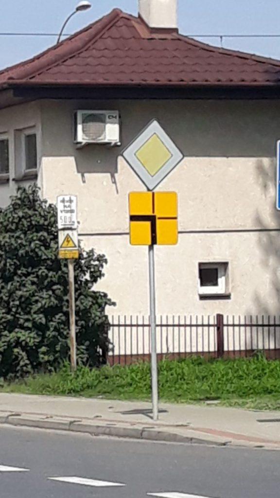 T-6a: tabliczka wskazująca rzeczywisty przebieg drogi z pierwszeństwem przez skrzyżowanie (umieszczana na drodze z pierwszeństwem)